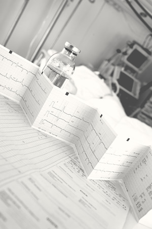 Nursing notes and test results on the table on the background of patient in the hospital ward.