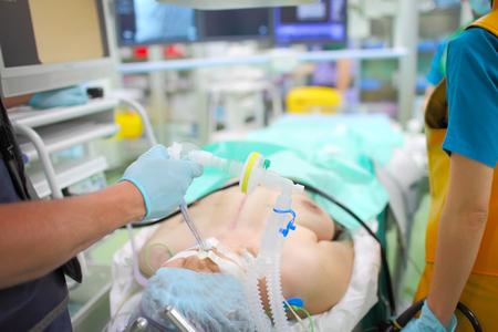 Patient inconscient connecté au ventilateur dans la salle d'opération à rayons X.
