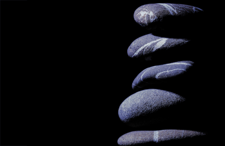 Smooth stones isolated on the black background with empty space for insertion.
