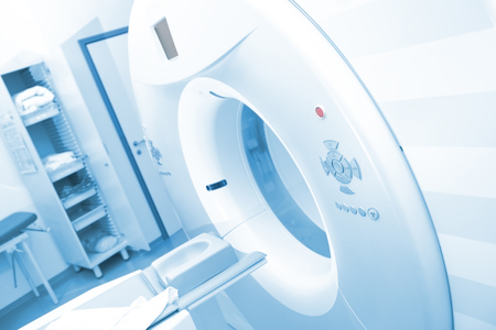 CT scan machinery with empty bed in the hospital room.