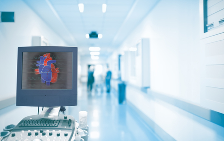 Ultrasonography equipment with heart image on the screen in the ER hallway with working doctors. Concept of an emergency care in a hospital with heart disease. Stok Fotoğraf