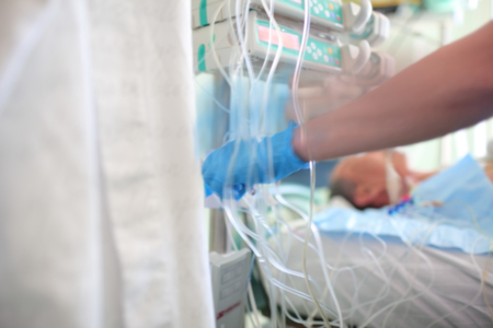 Patient in serious condition connected to a quantity of droppers and equipment in the department of intensive care. Stock Photo