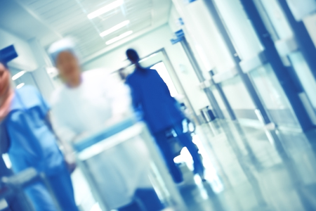 Blurred figures of walking medical staff in the hospital hallway, unfocused background. Imagens