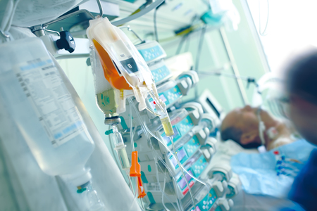 Medical infusion media on the background of the patient and the health worker in a hospital ward full of equipment.