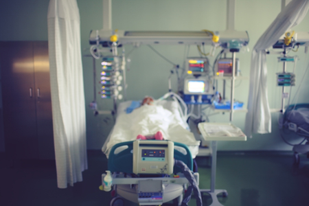 Ward in hospital with bed and lying heavy unhealthy patient. Blurred clinical background.