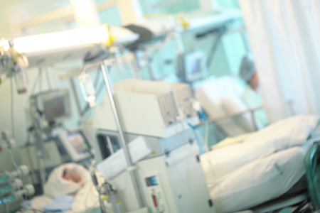 Patient in the intensive care unit surrounded by advanced life support equipment, unfocused background.
