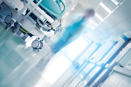 Medical bed in hospital hallway with professionals hurrying to the emergency case Stockfoto