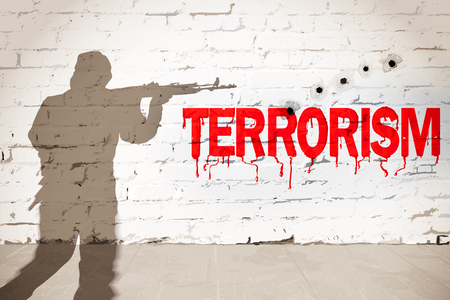 Terrorism concept. Red inscription on the shot brick wall