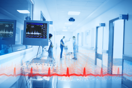 Red line of heartbeating on the background of digital equipment and medical doctors in the hospital hallway. Фото со стока
