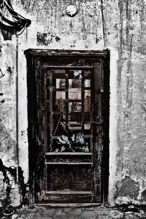 Rundown building with shabby wooden door. Foto de archivo - 132107101