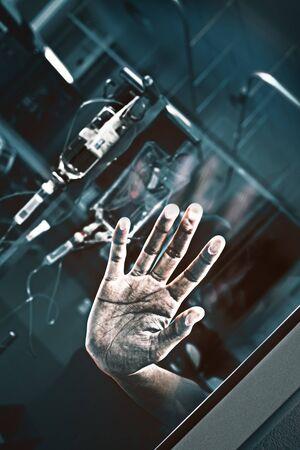 Vidrio de la sala con la palma del paciente presionada sobre el fondo de frascos de goteo intravenoso como concepto de tratamiento forzado. Foto de archivo