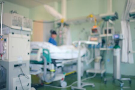 Critically ill patient surrounded by medical technologies in the ICU. Female doctor stands by patient bed working with equipment. Unfocused background.