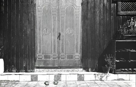 Old wooden doors with carved columns and arch in monochrome
