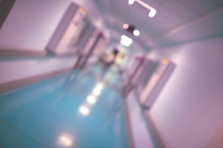 Lungo corridoio di un edificio ospedaliero, sfondo sfocato.
