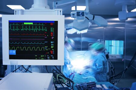 Heart monitor with multi-colored heartbeat lines against the group of working surgeons in the operating theatre. Stock Photo
