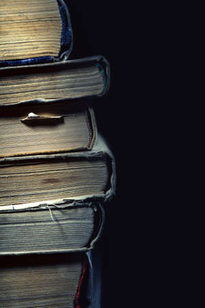 Stack of old dusty shabby books on black background.