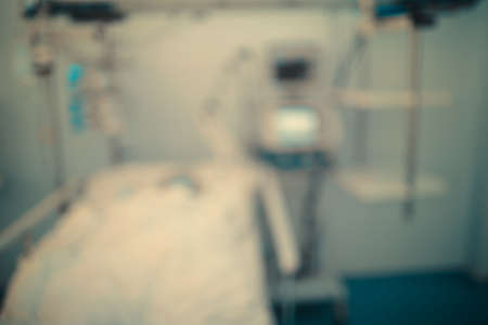 Critically ill patient is connected to a heart rate monitor in an intensive care unit, defocused background.