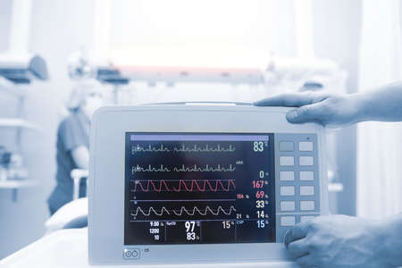 Medical workers connecting critical patient to the heart monitor in the intensive care unit.
