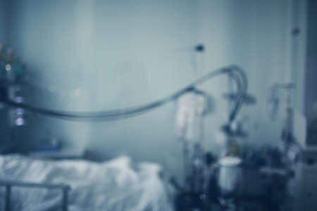 Hospital room with patient bed and medical equipment, defocused background.
