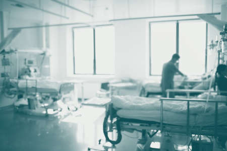 Doctor makes rounds of patients in intensive care unit, defocused background.