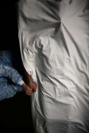 Female health worker holds the dead patient by hand, concept of death in the hospital. Reklamní fotografie
