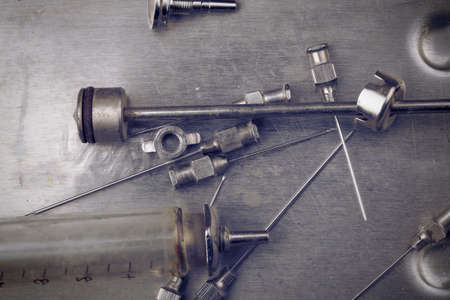 Retro nondisposable glass syringe on the dirty steel surface.