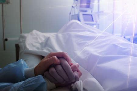 Female nurse holds dead male patient by the hand, concept of general nursing care. Reklamní fotografie