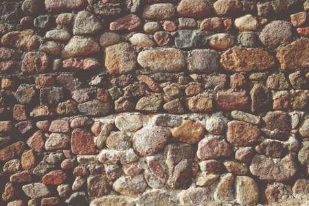 Old wall of large uneven stones as a textural background.