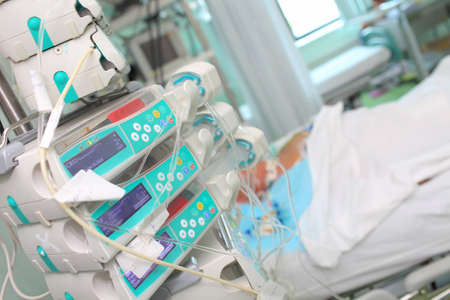 Intensive care unit with unconscious patient and advanced equipment.