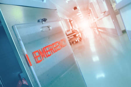 Emergency lettering on the wall and the bright light in the end of long hospital hallway.