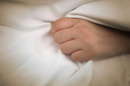 Female patient gripping a fistfull of the bed sheets in one hand.