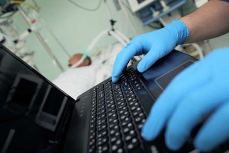 Doctor typing at the computer on the background of the patient in bed.