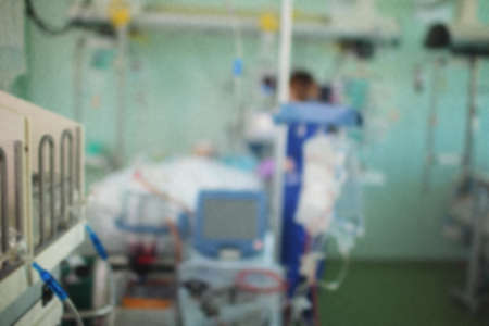 Nurse works with patient in the ICU, unfocused background.