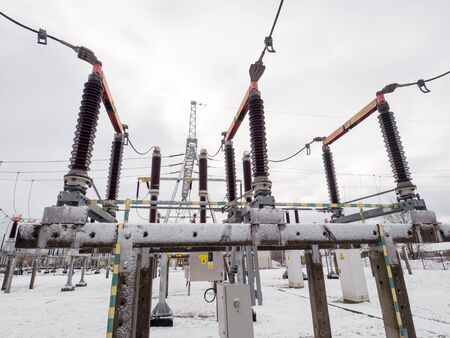 Power transmission system during winter. High voltage disconnector.
