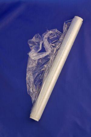 kunststoff rohr: Eine teilweise entrollte Rolle Folie  Frischhaltefolie vor einem blauen Hintergrund. Lizenzfreie Bilder