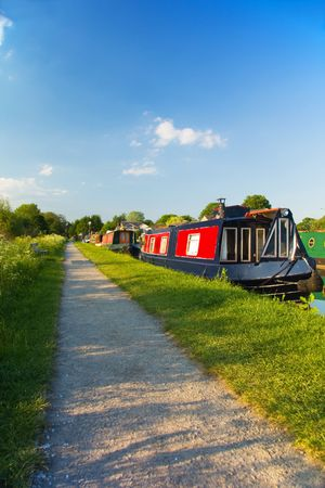 tethered: A beautiful evening by the canal with colourful narrow boat tethered for the night. Stock Photo