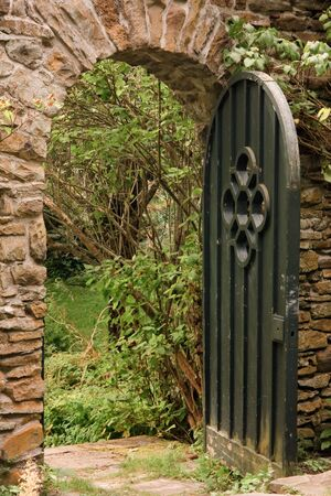 archway: Green gate leading through a wall into a garden beyond Stock Photo