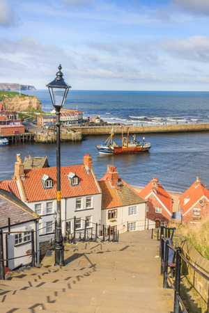 fishing fleet: One by one, the fishing fleet returns to Whitby Harbour.  Taken from the famous 199 steps.
