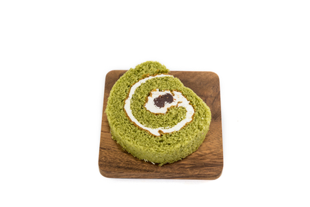 slice of swiss roll on wooden plate isolated on white background