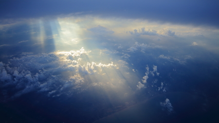 Rays of light shining through dark blue clouds on another cloud layer for background Stock Photo