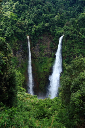 Tad Fan Waterfalls in southern Laos, high waterfall fall from lush jungle forest into inactive volcanic mount, Paksong high land. Tourist travel destination.