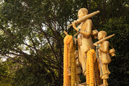 pilgrimage monk statues. golden colour statues of monks in walking stance situates under lush green ficus tree. worshipers placed flower garland on monk hand.