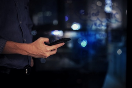 businessman checking on mobile phone in a modern office with out of focus lights in the background. office worker night at the office. modern businessman concepts.