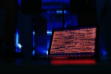 computer laptop in a dark room. computer displaying red code meaning problem, error, hacker or virus harming the system.
