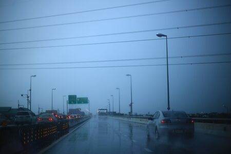 raining so much on a highway. dark atmosphere in a elevated road. street wet by a downpour. caught in a storm during a car drive. road safety and traffic due to poor weather.