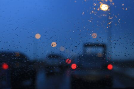 abstract background of car taillight bokeh. expressway road highway dusk and storm. twilight hour raining in the street. traffic congestion and time comes commuting from work to home.
