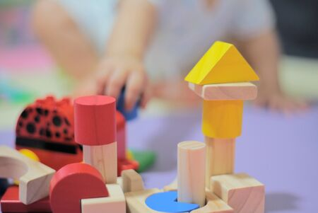baby playing analogue colorful wooden toy. creative play for children brain development. image focus on toys and baby sitting out of focus in the background. Reklamní fotografie