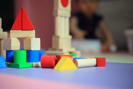 baby building a castle made of wooden blocks. children development process. blurred baby playing toy in a playpen.