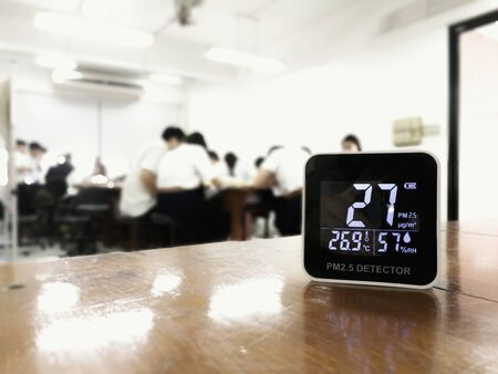 measuring indoor air quality. PM 2.5 (particulate matter) small dust particle pollution detector found higher than acceptable standard of dust in a classroom with students. harmful indoor environment
