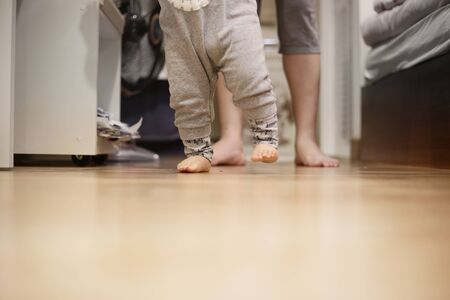 baby walking away from mother. small kid walk on bedroom wooden floor. mother sitting in wait. warm loving family concepts. happy moments of children growing up.